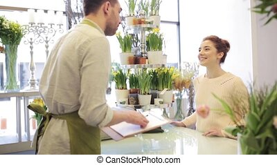 florist showing flowers to woman at flower shop