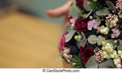 Florist shows finished flower arrangement on table inside office