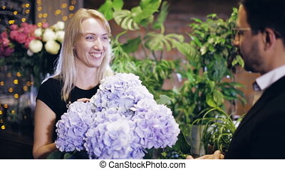 florist shows the buyer bouquets in a flower shop - female...