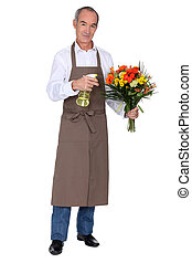 Florist spraying a bouquet of flowers