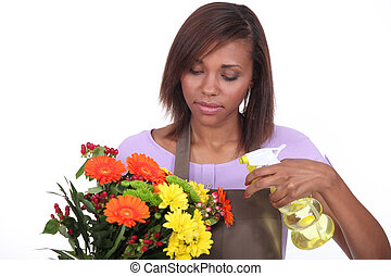 Florist spraying a bunch of flowers with water