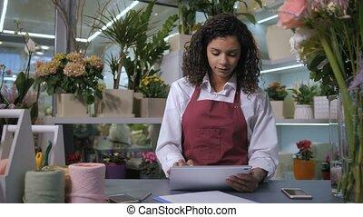 Florist taking orders using tablet in flower shop -...