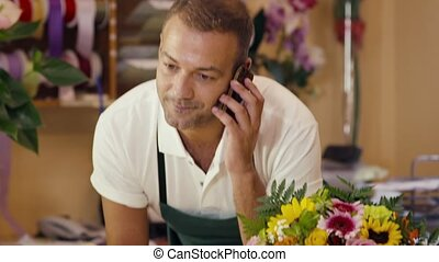 florist talking on telephone - portrait of mid adult man...
