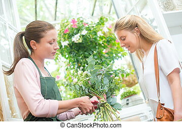 Florist trimming stems of flowers for customer