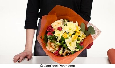 Florist turns a beautiful colorful bouquet. White. Close up
