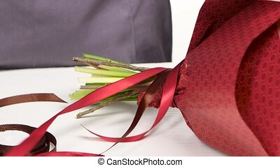 Florist tying a bow of ribbon on a bouquet of flowers. White. Close up