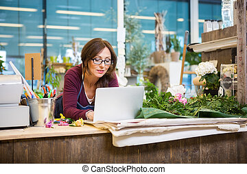 Florist Using Laptop In Flower Shop - Mid adult female...