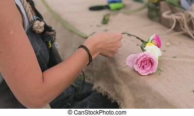 Florist weaves a wreath of fresh roses in the park