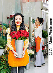 Florist with bucket of red roses