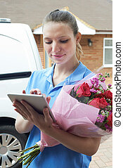 Florist With Digital Tablet Making Home Delivery Of Bouquet