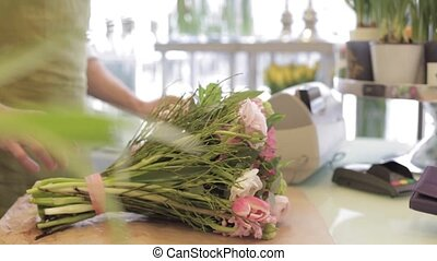 florist with flowers and customer at flower shop - people,...