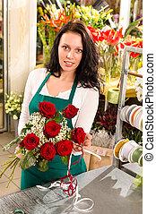 Florist woman arranging flowers roses shop working retail...