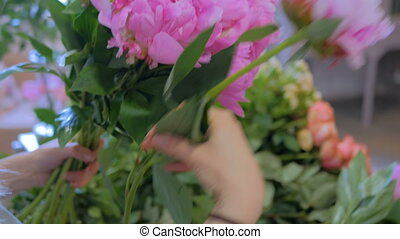 Florist woman making bunch at flower shop