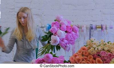 Florist woman making bunch at flower shop - Professional...