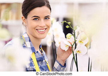 florist woman smiling with flowers orchids
