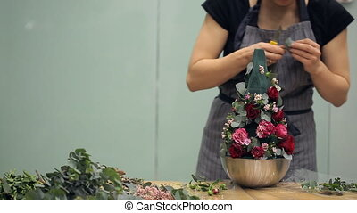 Florist works with floral composition explains technic on table inside
