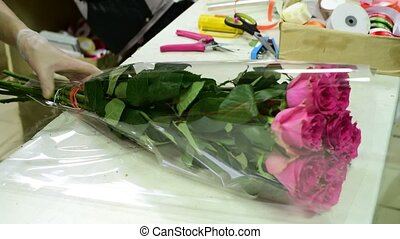 florist wrap a bouquet of roses in transparent package -...