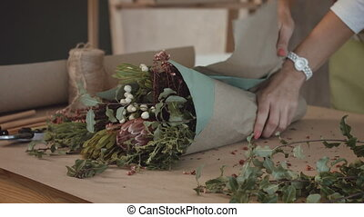 Florist wrapping flower bouquet in kraft paper