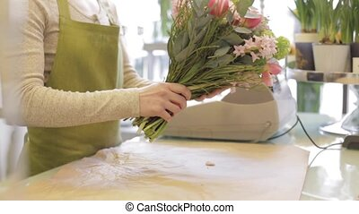 florist wrapping flowers in paper at flower shop - people,...