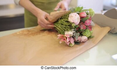florist wrapping flowers in paper at flower shop