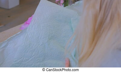 Florist wraps flowers in gift paper at flower shop