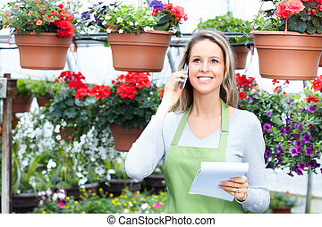 Young woman florist working in plant nursery.