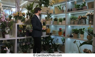 Floristical salon customer choosing potted flowers -...
