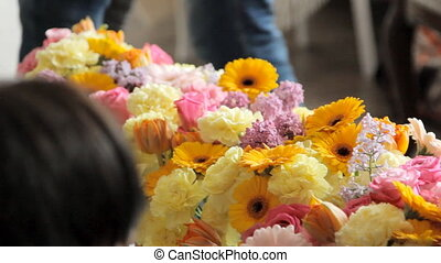 Florists decorate the room with flowers, such as roses, ...