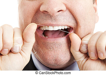 Flossing Teeth - Closeup of a man flossing his teeth with...