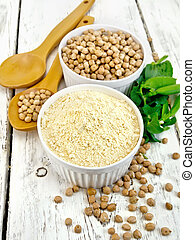 Flour chickpeas and chick-pea in white bowls and spoons, pods of green beans on the background of wooden boards