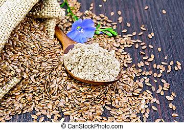 Flour flax in spoon with flower on dark board