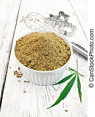 Flour hemp in bowl with leaf on board
