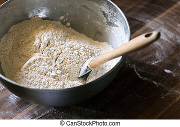Flour in a bowl with a spatula on a dark wooden background. Top view, place for text, close-up