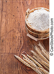 flour in wooden bucket with ears of wheat on old table