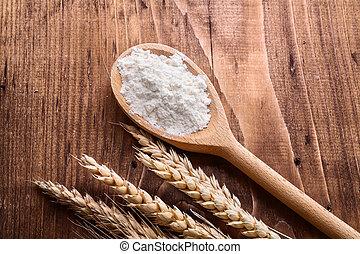 flour in wooden spoon with rye ears on vintage board