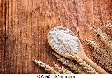 flour in wooden spoon with wheat ears on table copy