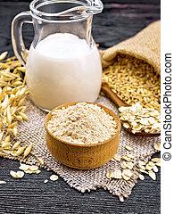Flour oat in bowl, milk in jug, oatmeal in spoon on burlap, grain in bag, oaten stalks against dark wooden board