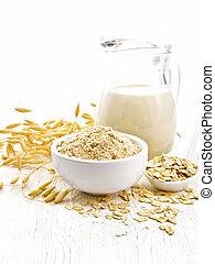 Flour oat in bowl, milk in a jug, oatmeal in spoon, oaten stalks on the background of wooden table