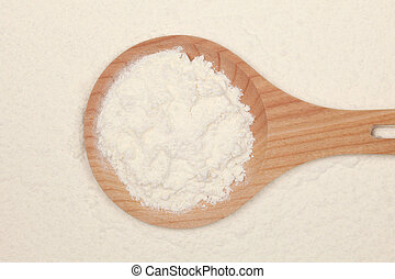 Flour on a wooden spoon forming a background