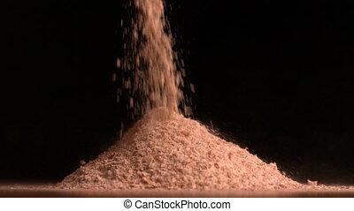 Flour pouring on black background