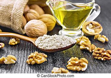 Flour walnut in spoon on dark board