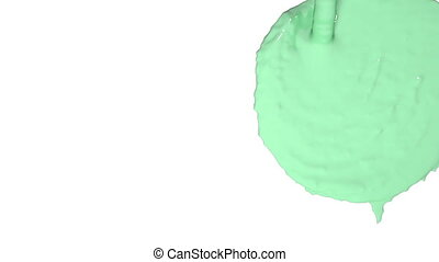 flow of green fluid fills a screen in slow motion.. Colored paint