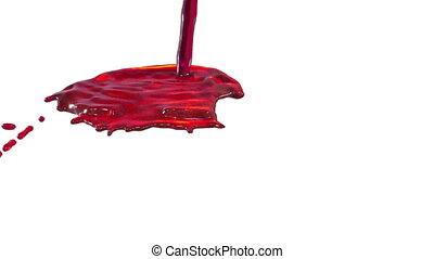 Flow of red liquid like juice splattering on white...