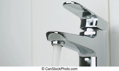 Flow of water is pouring from chrome-plated faucet