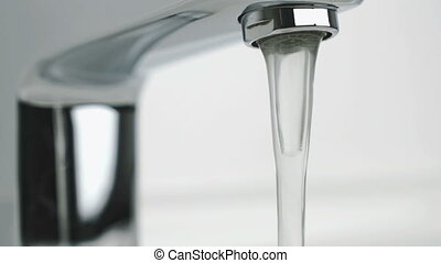 Flow of water pouring from chrome tap