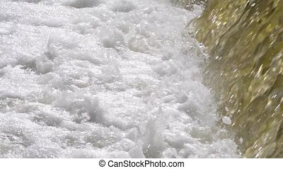 Flow of water with white foam close-up