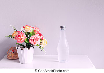 flower and bottle of water, on white table