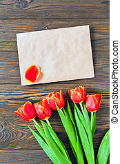 red tulips and kraft envelope on a wooden background - ...