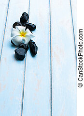 Flower, black stone on wood floor.