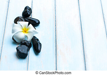 Flower black stone on wooden floor.
